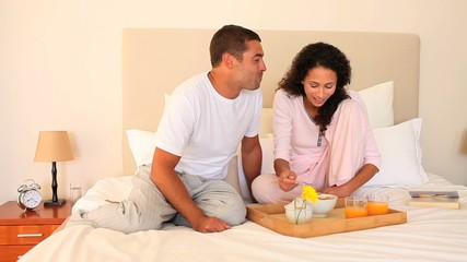 Young couple enjoying breakfast on tray on their bed