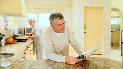 Mature man reading a newspaper in the kitchen