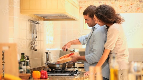 Young woman watching her boyfriend do the cooking