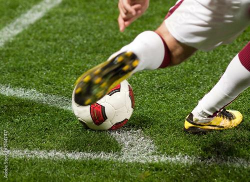 Piłkarz kopie piłkę z rogu