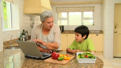 Woman giving her grandson a cookery lesson