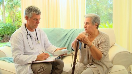 Doctor questioning patient while taking her blood pressure
