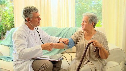 Doctor chatting while taking his patients blood pressure