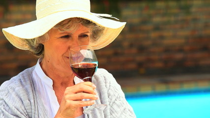 Woman tasting red wine outdoors