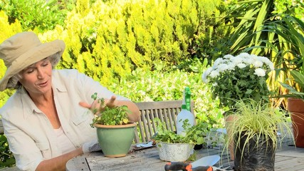 Mature woman smiling while potting a plant