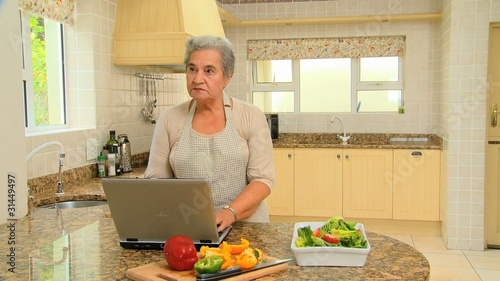 Elderly woman looking up a recipe on a laptop
