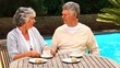 Couple sitting chatting over coffee by a swimming pool