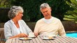 Mature couple sitting in the garden having tea and cake