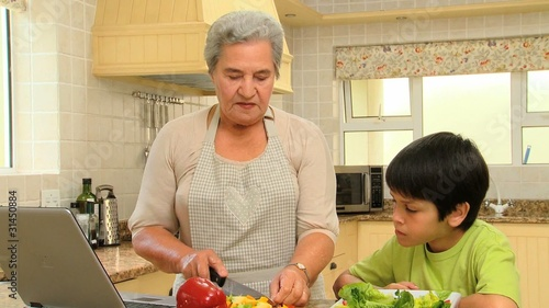 Little boy cooking with his grandmother