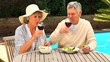 Mature couple drinking red wine in the garden