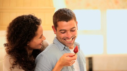 Woman taunting her boyfriend with a strawberry