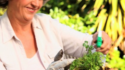Woman smiling and talking to her plant