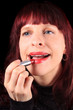 Applying lipstick to luscious lips