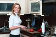 Beautiful happy woman in kitchen interior cuts a tomato