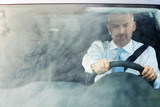 businessman driving car with sky reflections on windshield