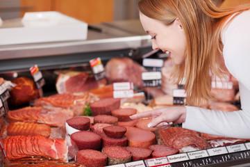 kundin in der metzgerei wählt salami aus