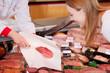 verkäuferin zeigt scheiben salami
