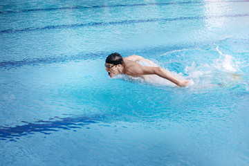 Swimmer in cap and goggles   performing the butterfly stroke