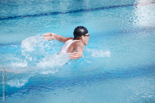 Swimmer  in competition swimwear performing the butterfly stroke