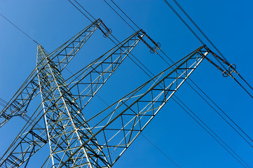 Part of an electricity pylon with blue sky on the background