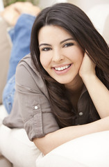 Beautiful Hispanic Woman Laying on Sofa Relaxing & Smiling