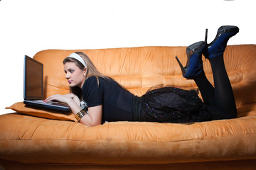 Smiling girl on sofa with laptop