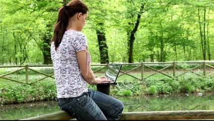 Ragazza che lavora al pc in riva a un lago