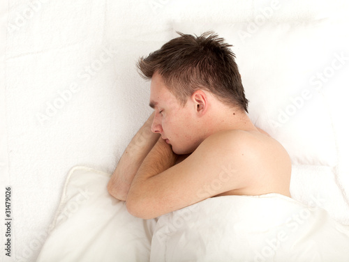 sleeping young handsome man in white bedding, series