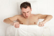 curious young handsome man in white bedding, series