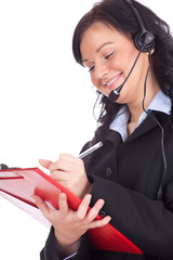 smiling call center woman in headset writing on clipboard