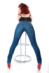 sexy young red-haired woman in black corset and blue jeans
