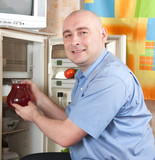 man putting jug into refrigerator