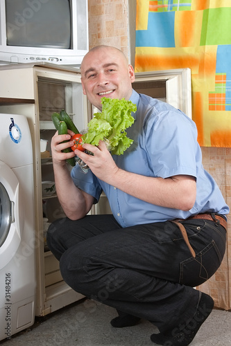 Adult man putting fresh vegetables