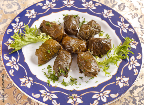 vine leaves stuffed with rice (dolmades served on a plate)