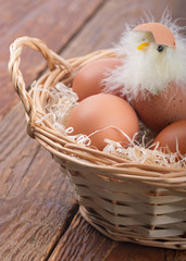 Hatched chicken in a basket with eggs on the table