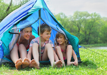 Happy mother and her kids in swimsuit sit in blue tent