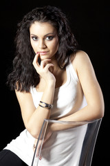 Young beautiful brunette female sitting on the chair