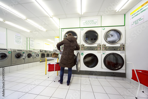 woman put laundry in washing machine in public laundry