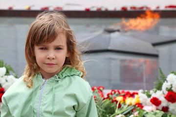beautiful little girl stands near memorial, eternal flame
