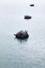 Two underwater mines on water surface