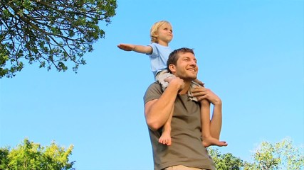 Little boy sitting on his father' shoulders