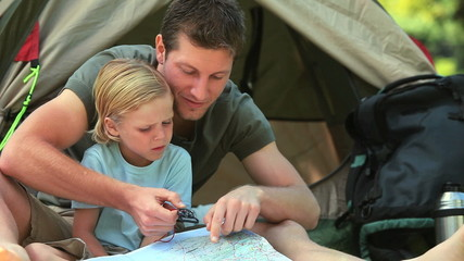 Father teaching  his son to use a map