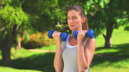 Dynamic woman using dumbbells