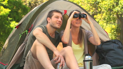 Attractive couple looking through binoculars