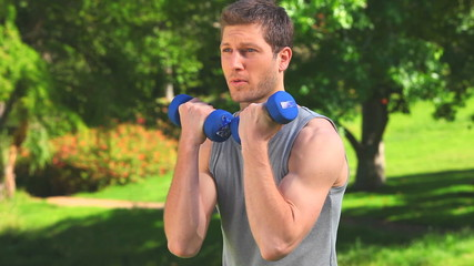 Brown-haired man using dumbbells