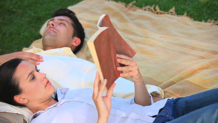 Man taking a nap while his girlfriend is reading a book