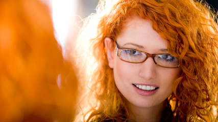 Attractive girl wearing glasses looking at a mirror.