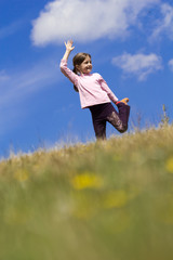 Girl jumping on the meadow, with blue sky and clouds in backgrou