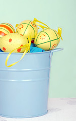 colorful easter eggs in a blue pail