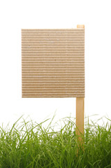 cardboard sign with grass isolated on a white background
